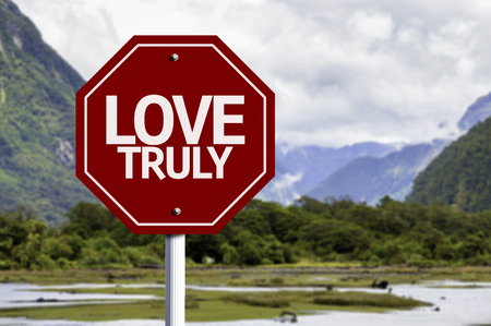 truly: Love Truly written on the road sign with valley background