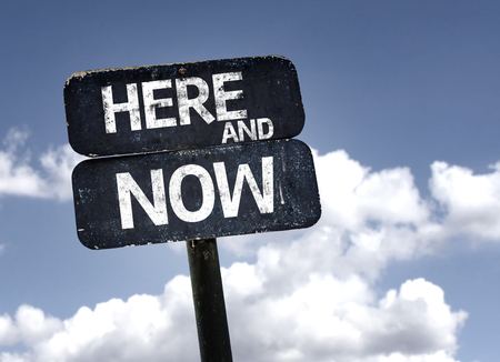 Here and Now sign with clouds and sky background
