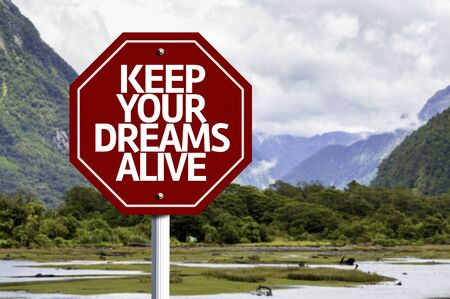 alive: Keep Your Dreams Alive written on the road sign with valley background
