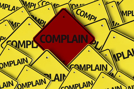 complain: A red road sign amongst multiple road signs with text: Complain Stock Photo