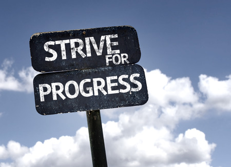 strive for: Strive For Progress sign with clouds and sky background Stock Photo
