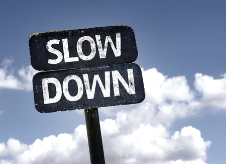 Slow Down sign with clouds and sky background Stock Photo