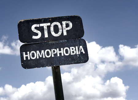homophobia: Stop Homophobia sign with clouds and sky background