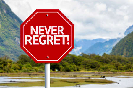 regret: Never Regret written on the road sign with valley background