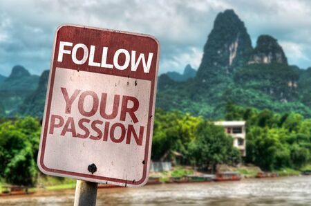 Follow Your Passion written on the road sign in a valley