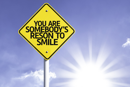 curare teneramente: You are somebodys reason to smile sign with sunny background