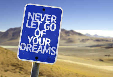 let go: Never let go of your dreams sign with desert background