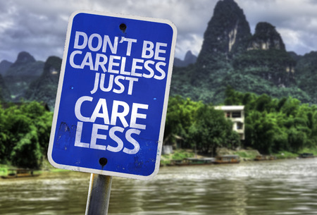 careless: Dont be careless just care less sign with wetland background Stock Photo