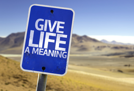 meaning: Give life a meaning sign with desert background Stock Photo