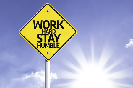 respectful: Work hard stay humble sign with sunny background Stock Photo