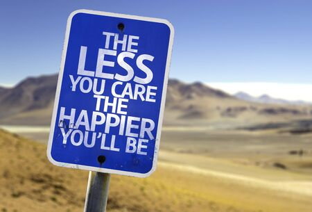 happier: The less you care the happier youll be sign with desert background