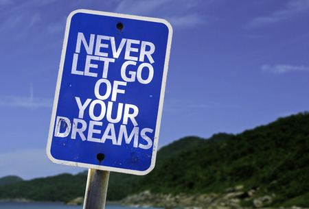 let go: Never let go of your dreams sign with beach background