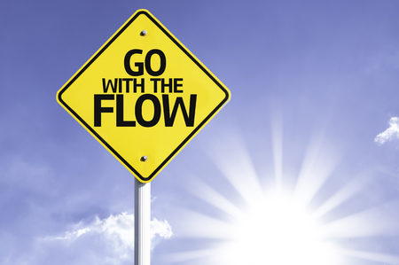 Go with the flow sign with sunny background