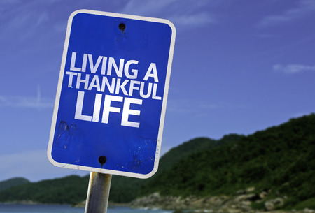 living wisdom: Living a thankful life sign with beach background