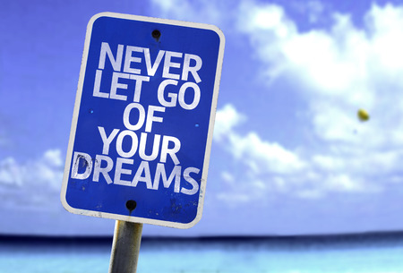 let go: Never let go of your dreams sign with sea background Stock Photo