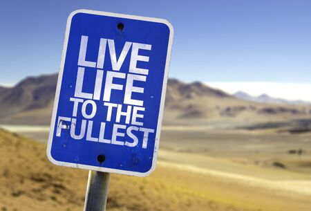 Leef het leven tot het volledigste bord met woestijnachtergrond Stockfoto
