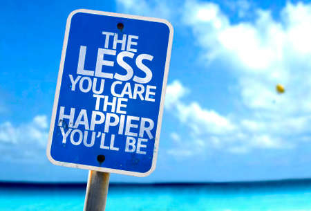 happier: The less you care the happier youll be sign with sea background