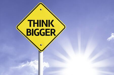 bigger: Think bigger sign with sunny background
