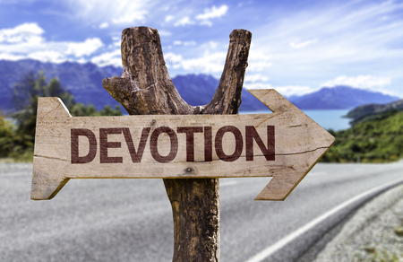 Devotion sign with arrow on road background Stock Photo
