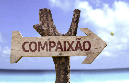 Compaixao (compassion in Portuguese) sign with arrow on beach background