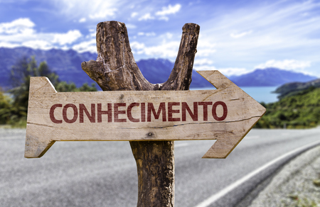 Conhecimento (knowledge in Portuguese) sign with arrow on road background