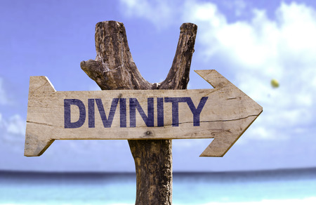 divinity: Divinity sign with arrow on beach background