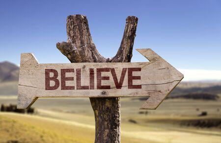 believe: Believe sign with arrow on desert background Foto de archivo