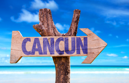 cancun: Cancun sign with arrow on beach background