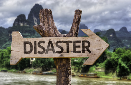 Wooden sign board in wetland with text: Disaster Stock Photo