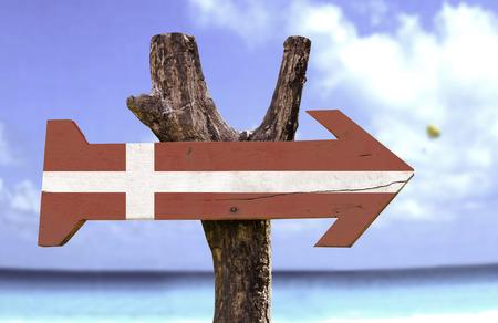 Denmark flag sign with arrow on beach background