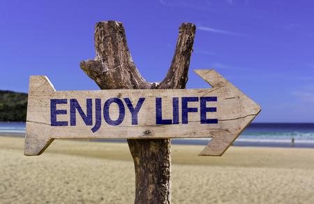 Geniet van het levensteken met pijl op strandachtergrond Stockfoto