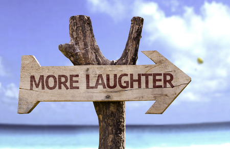 laughter: More laughter sign with arrow on beach background