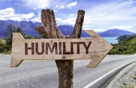humildad: signo de la humildad con la flecha en el fondo de carreteras