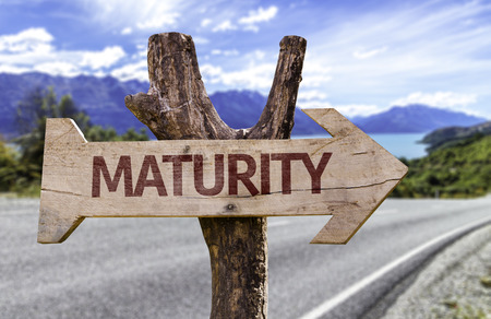 adulthood: Maturity sign with arrow on road background