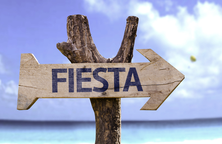 Fiesta (party in Spanish) sign with arrow on beach background