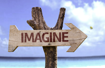 Imagine sign with arrow on beach background