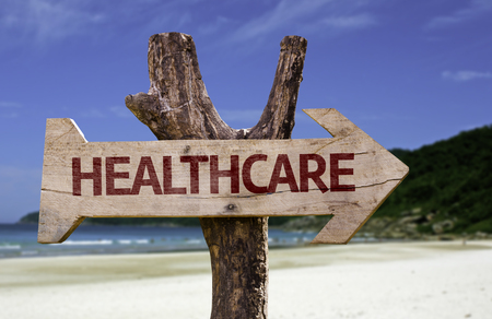 Healthcare sign with arrow on beach background