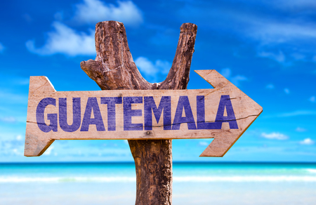 Guatemala sign with arrow on beach background