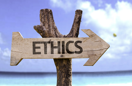 Ethics sign with arrow on beach background
