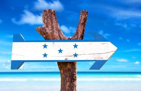 bandera de honduras: Honduras flag sign with arrow on beach background