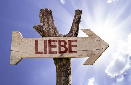 Liebe: Liebe (love in German) sign with arrow on sunny background