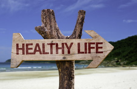 Healthy life sign with arrow on beach background