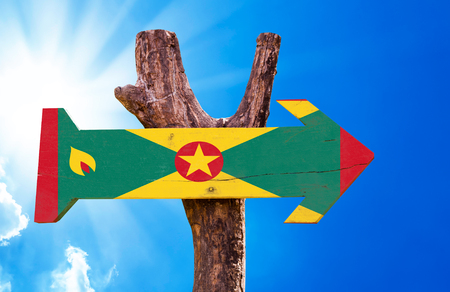 grenada: Grenada flag sign with arrow on sunny background