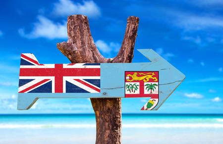 Fiji flag sign with arrow on beach background photo