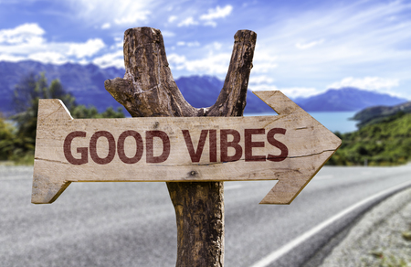 Good vibes sign with arrow on road background Stock Photo