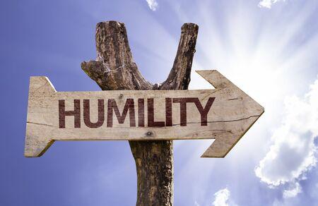 humility: signo de la humildad con la flecha en el fondo de sol Foto de archivo