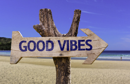 positivism: Good vibes sign with arrow on beach background