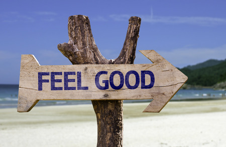 Feel good sign with arrow on beach background Stock Photo