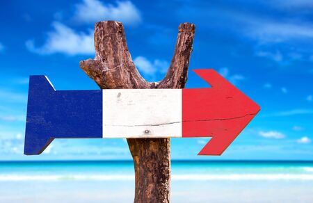 french way: France flag sign with arrow on beach background Stock Photo