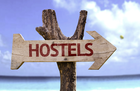 Hostels sign with arrow on beach background Stock Photo